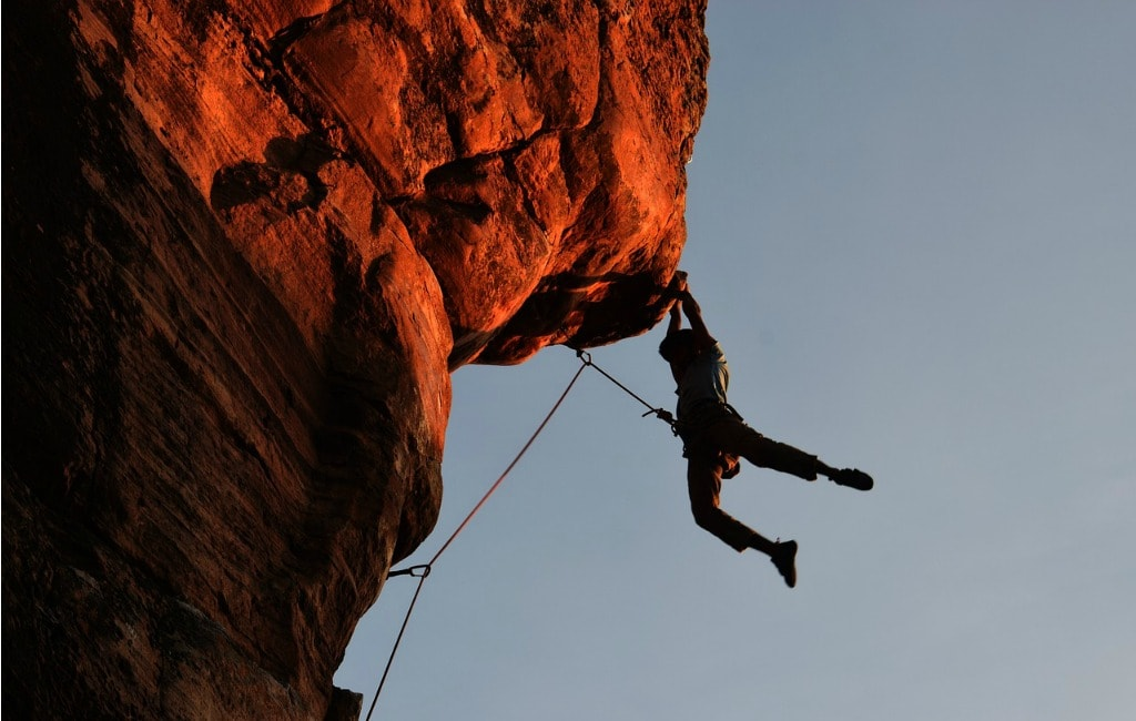 man rock climbing mountain
