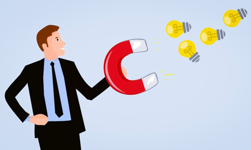 man with magnet, man pulling business ideas, idea bulb towards magnet