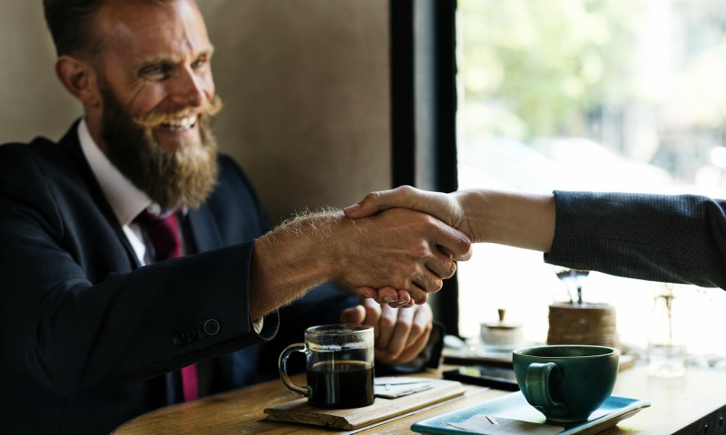 sales person smiling and shaking hand after closing the deal and winning the client