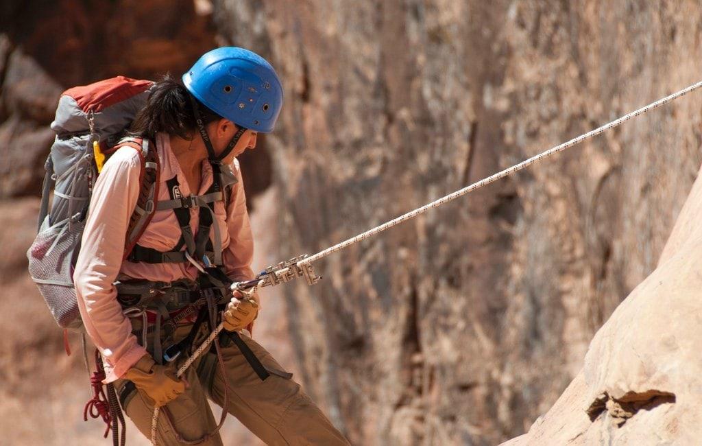 girl climbing mountain rope blue helmet