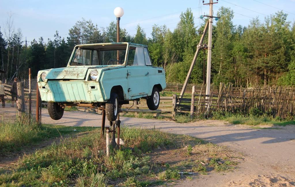 car hanging on tube light pole on road side