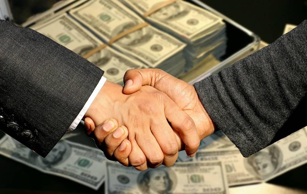 professional men handshake for closing deal in front of money